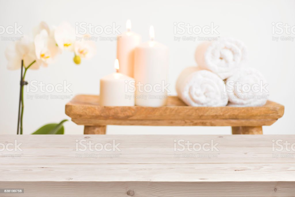 Wooden table in front of blurred background of spa products stock photo
