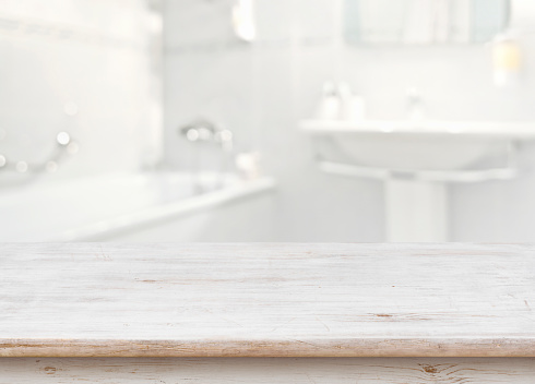 istock Wooden table in front of blurred bathroom interior as background 669872674