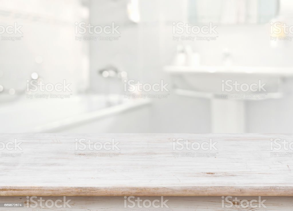 Wooden table in front of blurred bathroom interior as background stock photo