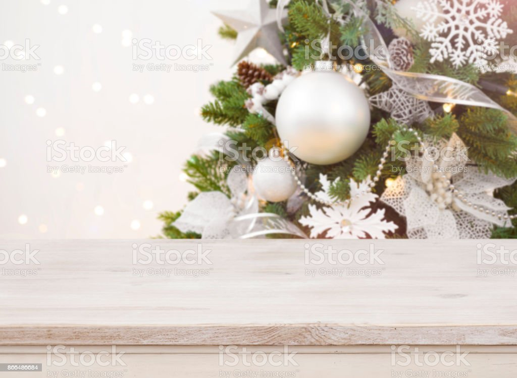 Wooden table in front of blurred decorated Christmas tree background stock photo