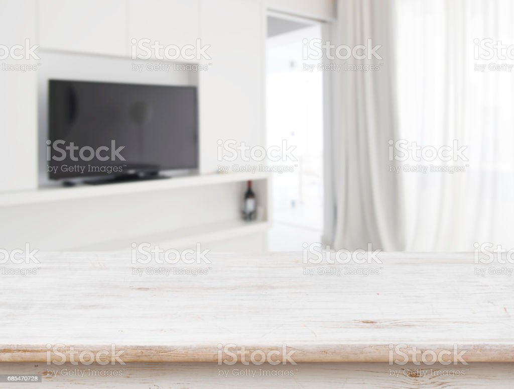 Wooden table in front of blurred living room interior background stock photo