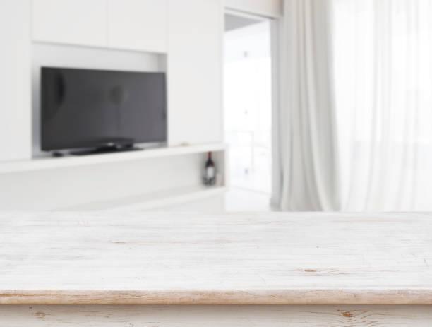 holztisch vor verschwommenem wohnzimmer-innenhintergrund - zimmer bildschirm stock-fotos und bilder