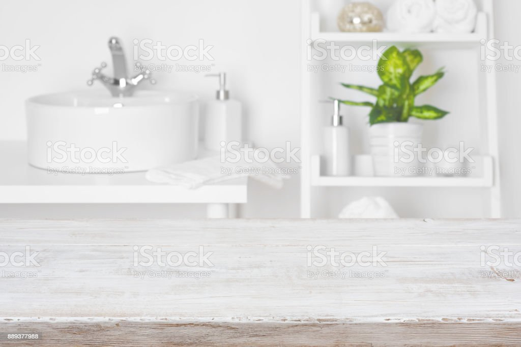 Wooden table in front of blurred white bathroom shelves background stock photo