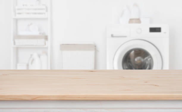 Wooden table in front of defocused washing machine and laundry stock photo