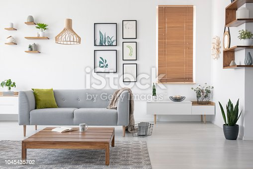 istock Wooden table in front of grey settee in natural living room interior with blinds and gallery. Real photo 1045435702