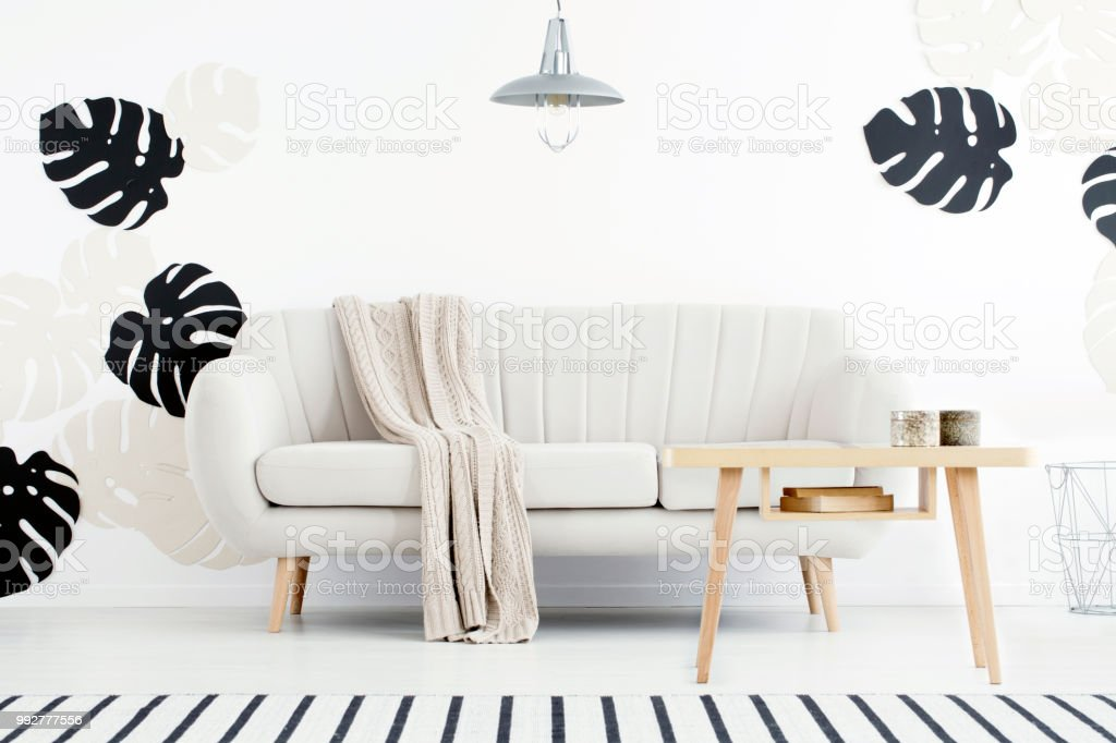 Wooden table in front of settee with blanket in white flat interior with monstera leaves. Real photo