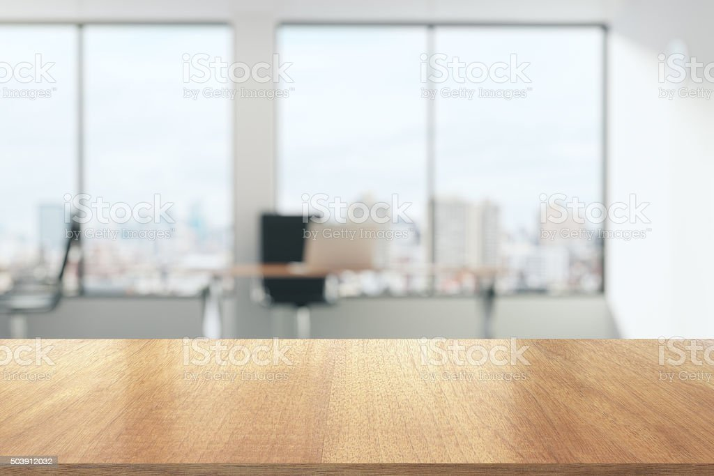 Wooden table in sunny office with big windows stock photo