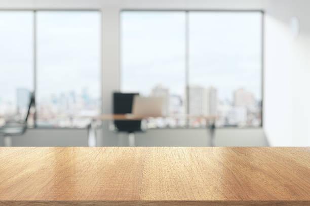 Mesa de madera en la soleada oficina con grandes ventanales - foto de stock
