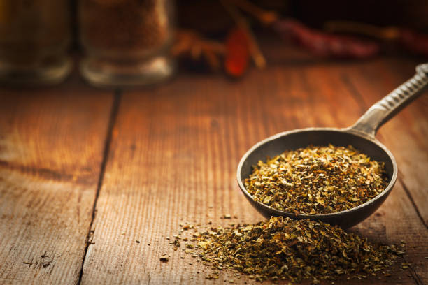 Wooden table of colorful spices. Marjoram leaves spilling from a measuring spoon. Background zaatar spice stock pictures, royalty-free photos & images