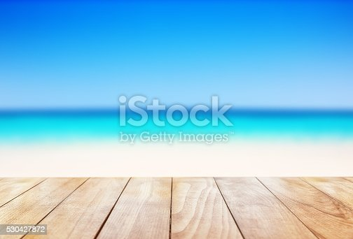 istock Wooden table on blue sea and white sand beach 530427872