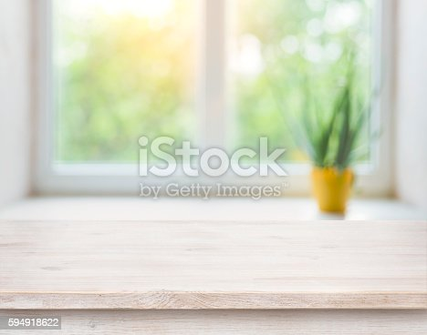 istock Wooden table on blurred autumn window with plant pot background 594918622
