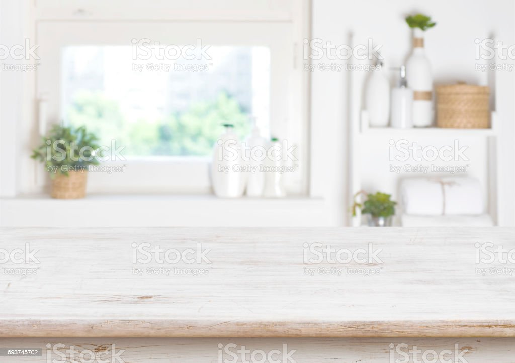Wooden table on blurred background of bathroom window and shelves stock photo