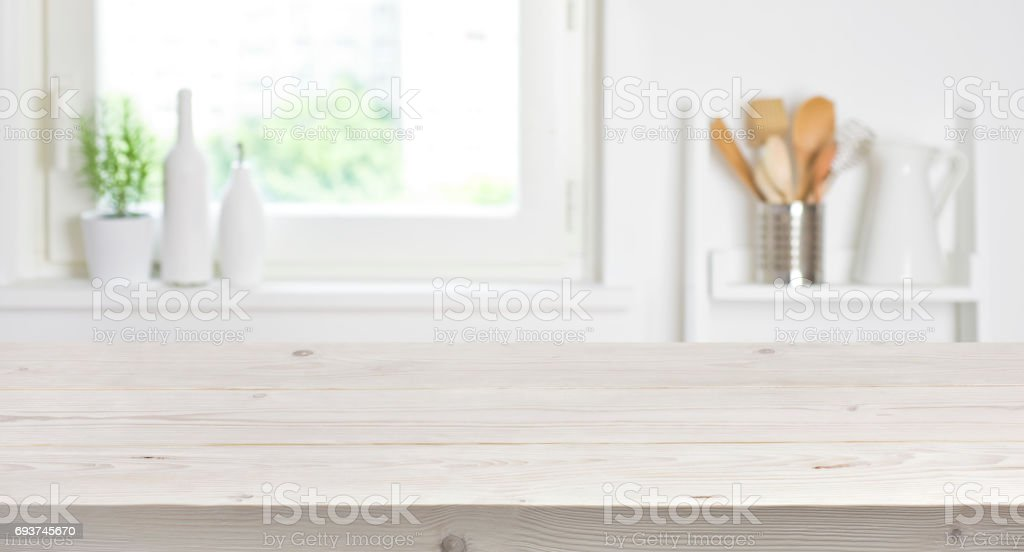 Wooden table on blurred background of kitchen window and shelves stock photo