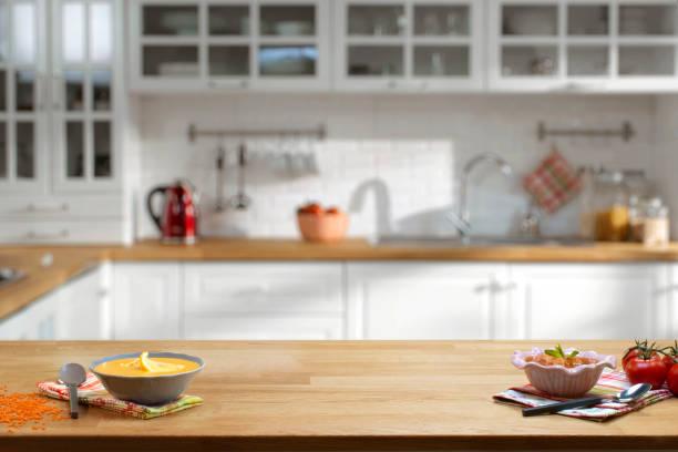 holztisch auf unscharfen küche interieur hintergrund - küche lila stock-fotos und bilder