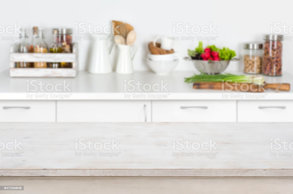 Wooden table on blurred kitchen interior background with fresh vegetables stock photo