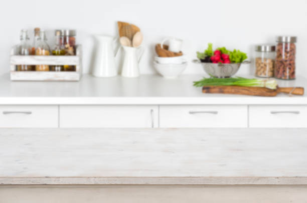 Wooden table on blurred kitchen interior background with fresh vegetables – zdjęcie