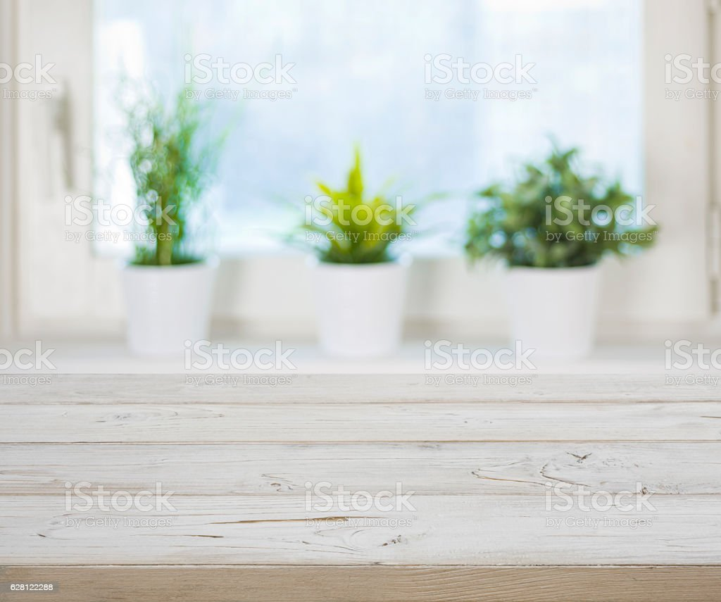 Wooden table on blurred spring window with plant pots background stock photo