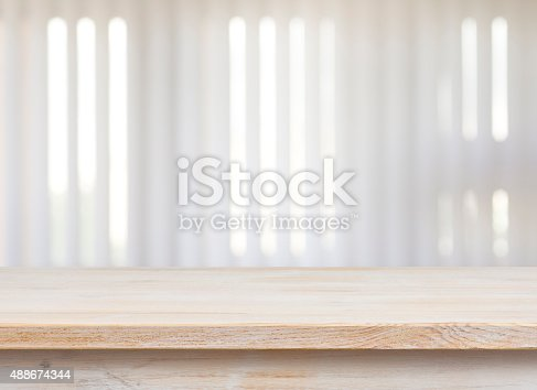 Wooden table on defocuced window with jalousie background