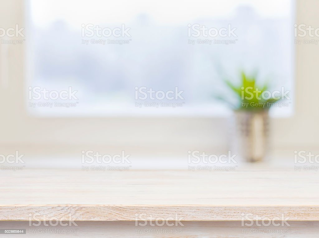 Wooden table on defocuced winter window background stock photo