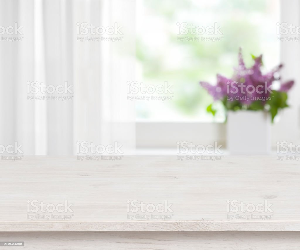 Wooden table on defocused window with purple flower pot background stock photo