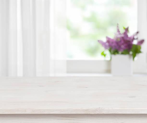 holztisch auf unscharf fenster mit lila blumentopf hintergrund - küche lila stock-fotos und bilder