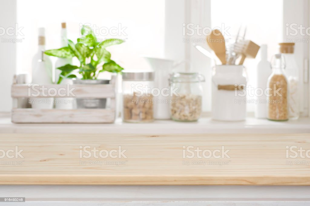 Wooden table over blurred kitchen window sill for product display stock photo