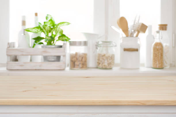 wooden table over blurred kitchen window sill for product display - kitchen situations foto e immagini stock