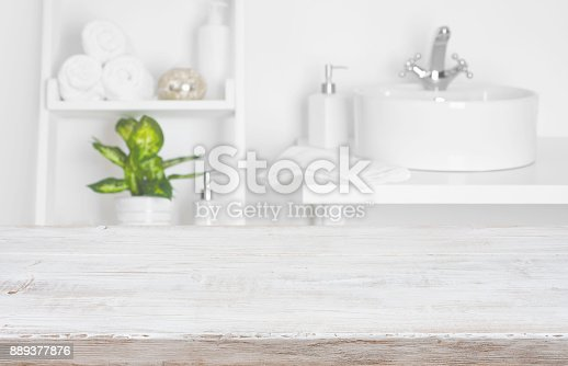 istock Wooden table over blurred spa salon bathroom shelves background 889377876