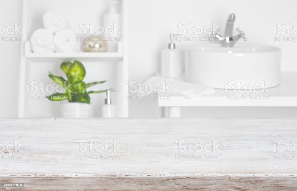 Wooden table over blurred spa salon bathroom shelves background stock photo