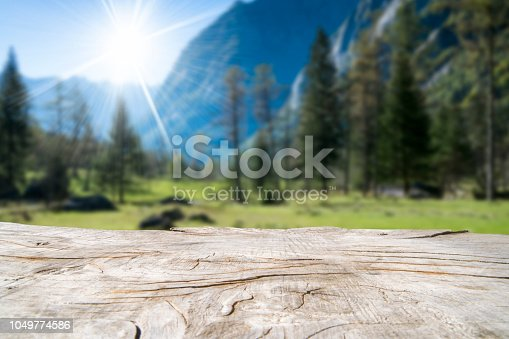 Empty wooden table with blurred mountain outdoor background. Ready for product montage.