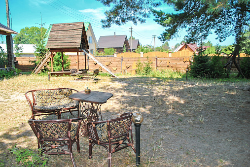 Wooden table, sofa, armchairs and kids slide in summer backyard. Garden furniture and playground near wooden fence