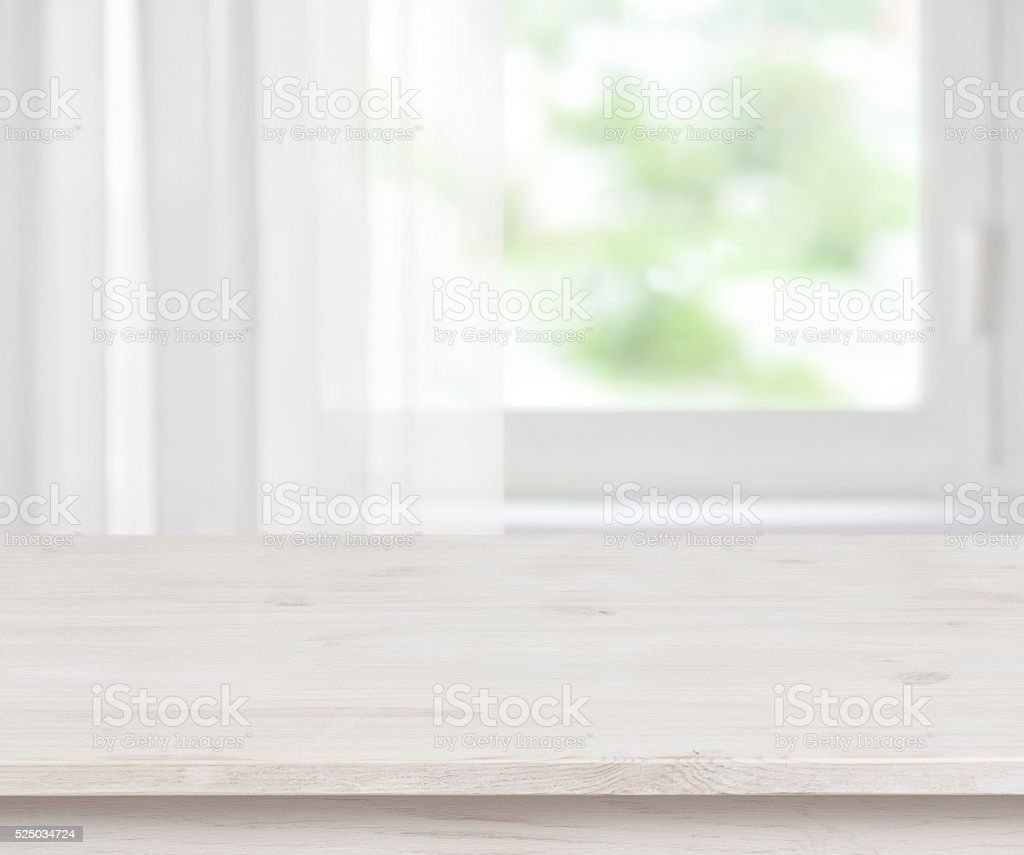 Wooden table surface on defocused half curtained window background stock photo