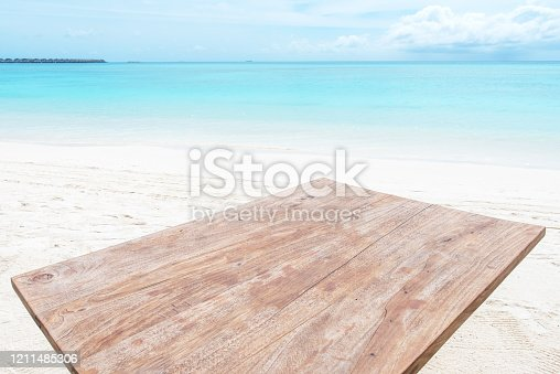 677933036 istock photo Wooden table surface with tropical beach background 1211485306