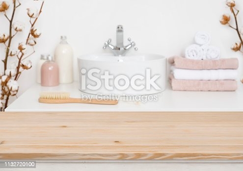819534860istockphoto Wooden table top and blur bathroom interior on the background 1132720100