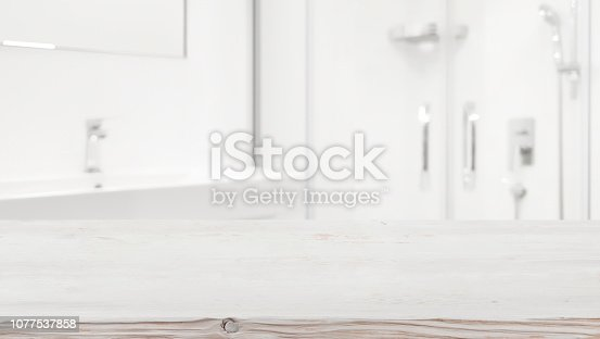 istock Wooden table top and blurred white bathroom interior as background 1077537858