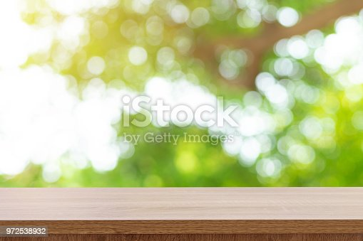 641254964 istock photo Wooden table top and green bokeh display montage for product with space. 972538932