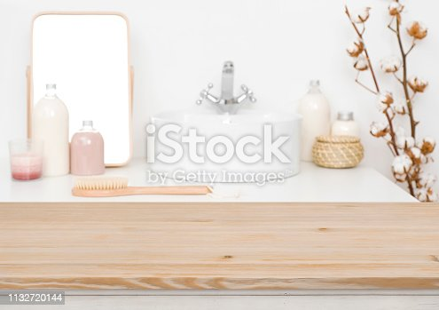 819534860istockphoto Wooden table top for product display and blurred bathroom background 1132720144