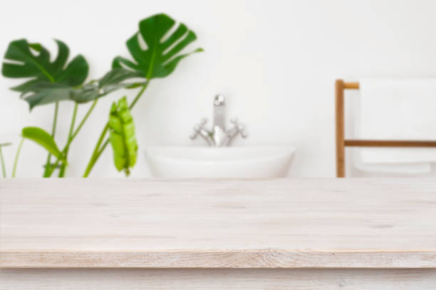 Wooden table top for product display over blurred bathroom interior stock photo