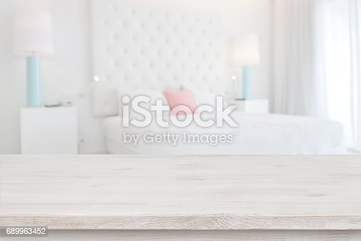 istock Wooden table top in front of blurred bedroom interior background 689963452