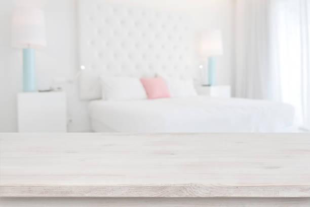 hölzerne tischplatte vor verschwommenem schlafzimmer-innenhintergrund - hellrosa zimmer stock-fotos und bilder