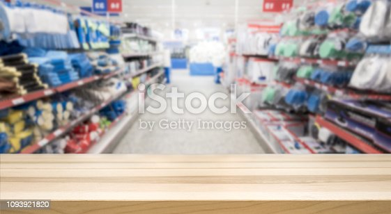istock Wooden table top in front of blurred hardware and grocery store. 1093921820