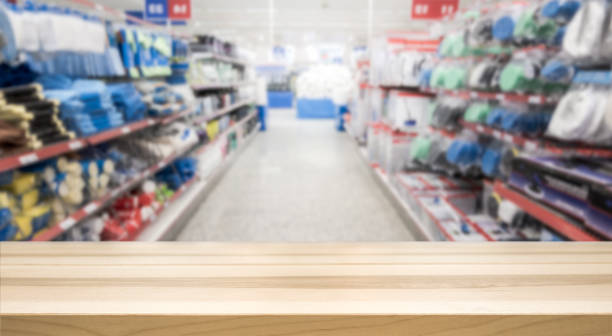 Wooden table top in front of blurred hardware and grocery store. Wooden table top in front of blurred hardware and grocery store. Background for product display montage. Copy space design. retail equipment stock pictures, royalty-free photos & images