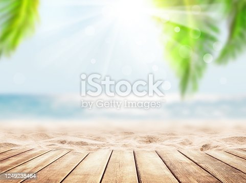 istock Wooden table top on blue sea and white sand beach background. 1249238464