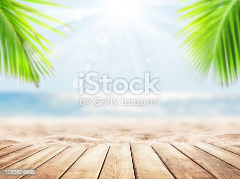 Wooden table top on blue sea and white sand beach background. Vacation holidays background wallpaper.