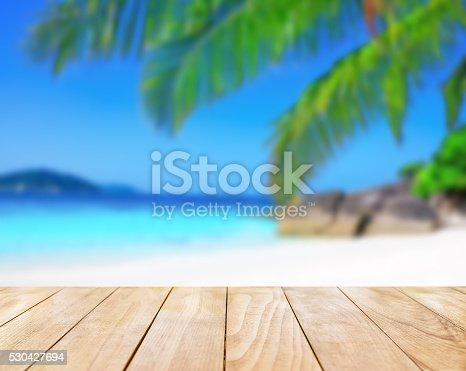 istock Wooden table top on blue sea and white sand beach 530427694