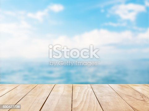 istock Wooden table top on blue sea and white sand beach 530427736