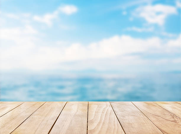 Wooden table top on blue sea and white sand beach stock photo