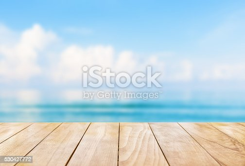 istock Wooden table top on blue sea and white sand beach 530427772