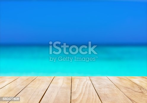 istock Wooden table top on blue sea and white sand beach 530427808