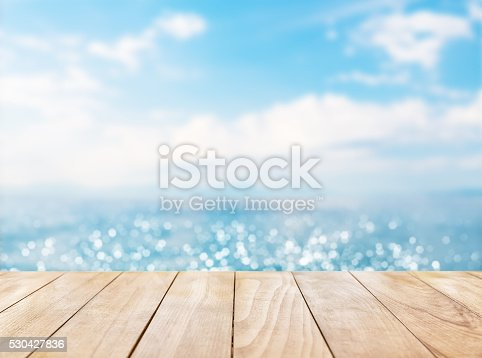 530427836istockphoto Wooden table top on blue sea and white sand beach 530427836
